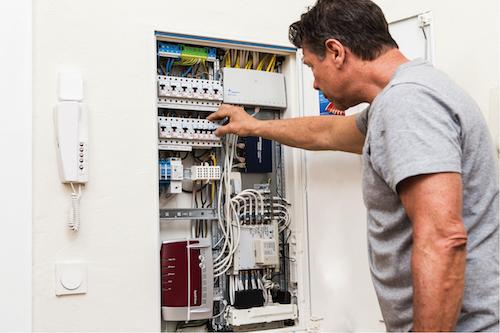 Das Innenleben eines fast vollbepackten Verteilerkastens für ein vernetztes Wohnhaus zeigt nicht nur Farbe, sondern auch eine verwirrende Vielfalt von Drähten und Geräten. Modems, Router, Transformatoren