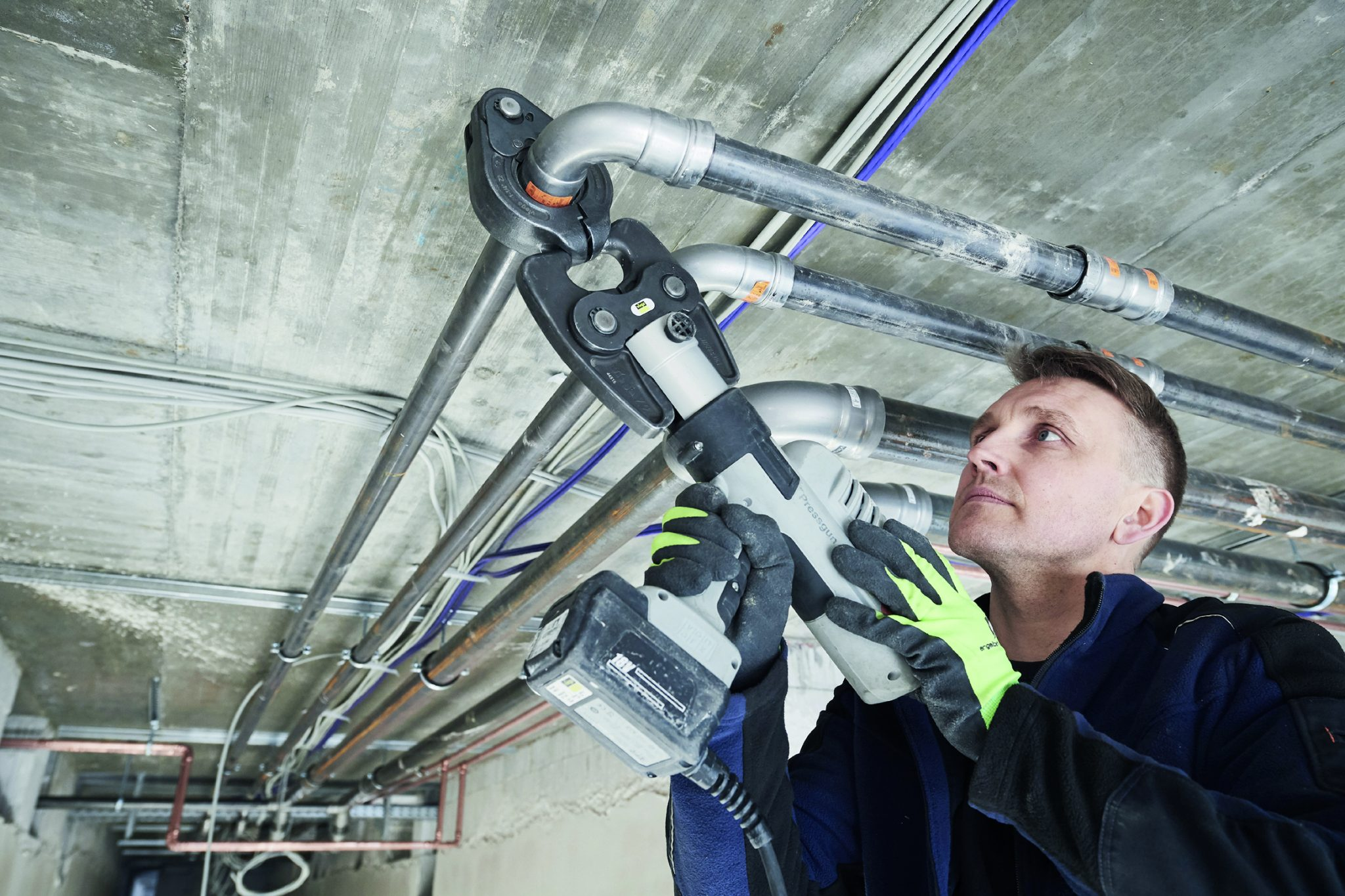 """Für SHK-Installateur Uvis Eglitis ist im Vergleich zum wesentlich aufwändigeren Schweißen die """"Megapress""""-Pressverbindungstechnik gerade bei Arbeiten dicht unter der Hallendecke eine große Erleichterung."""